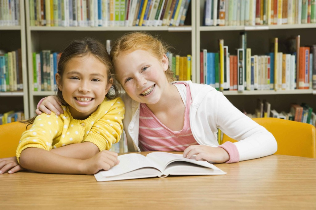 smiling girls in library with book